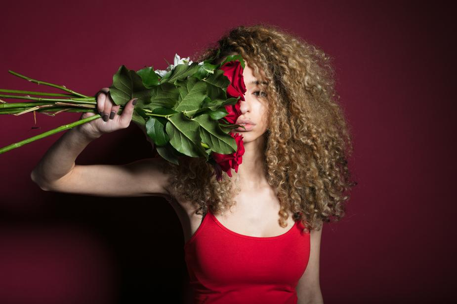 Girl holds flowers against pinkish backdrop