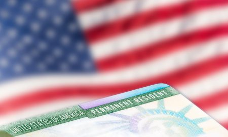 United States of America permanent resident card, green card, with US flag in the background. Legal immigration concept.